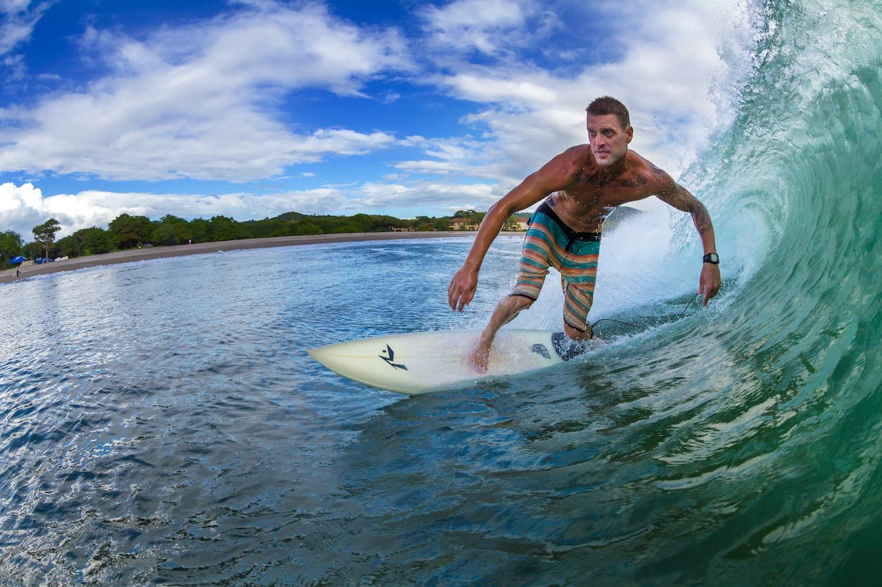 A foreigner surfing enjoying a perfect wave in Playa Santana, in southern Nicaragua beach in Central America