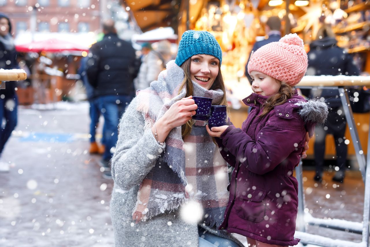 Adorable child and beautiful mum on Christmas market in Germany