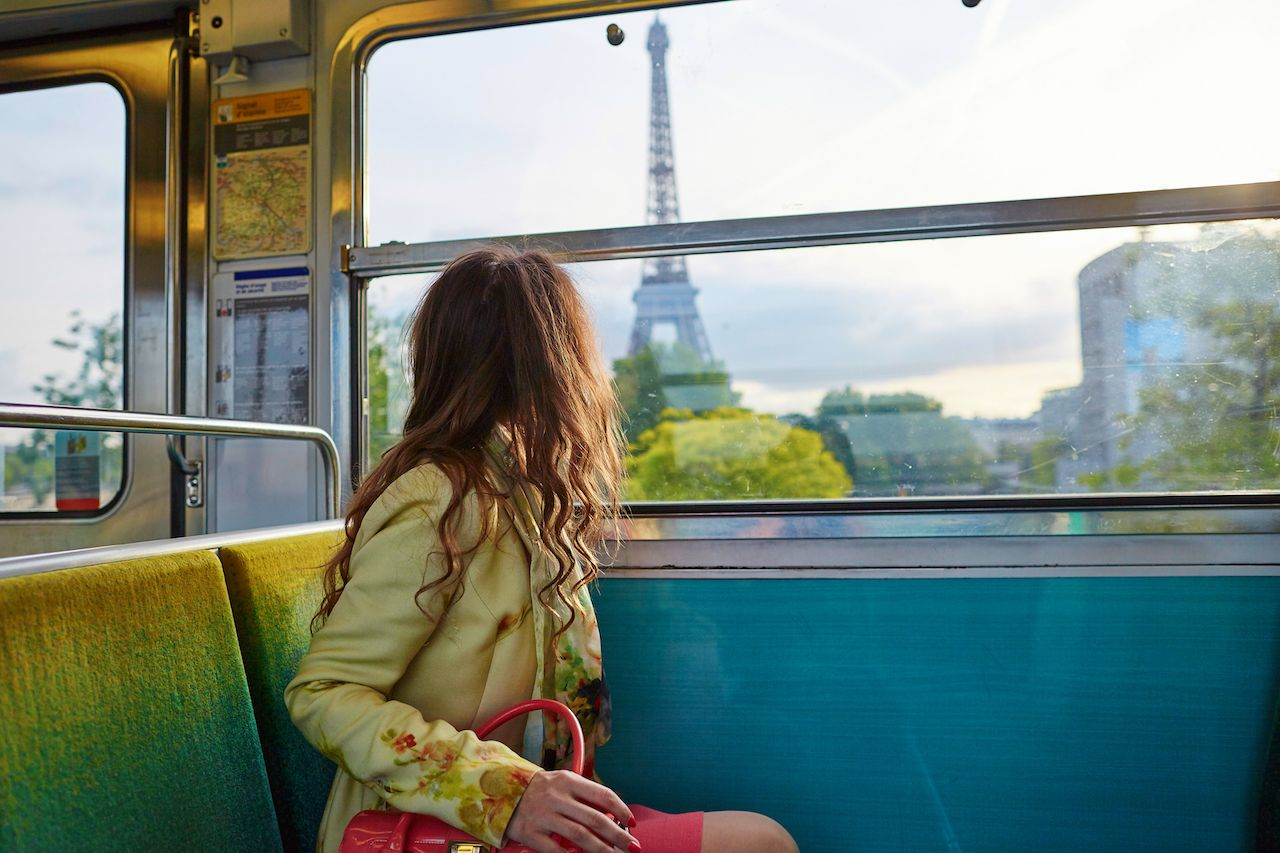 Beautiful young woman traveling in a Parisian underground train and looking through the window at the Eiffel tower