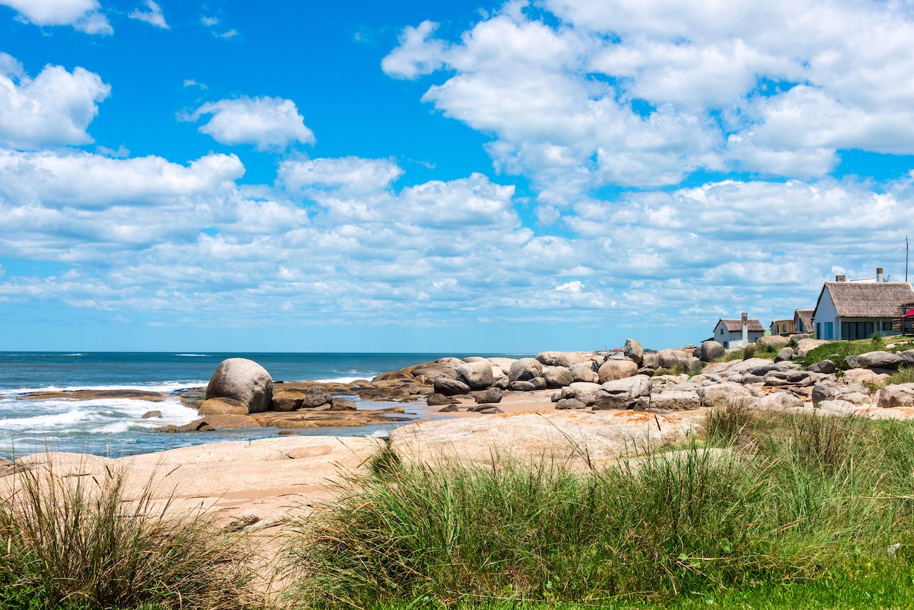 Boulders, green grass, and seaside houses at Punta del Diablo, a popular beach in Uruguay