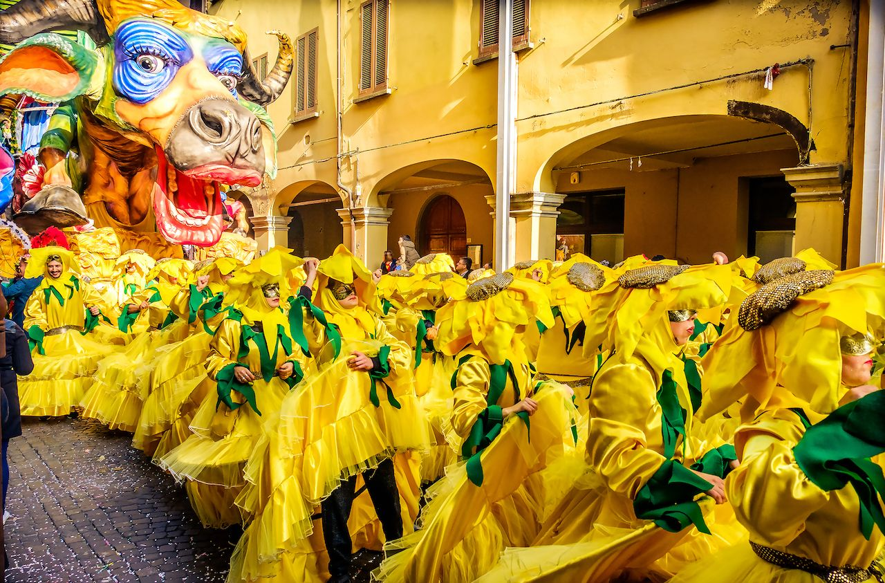 Carnevale di Cento paper cow coward parade float with people choreography in yellow sunflower costumes