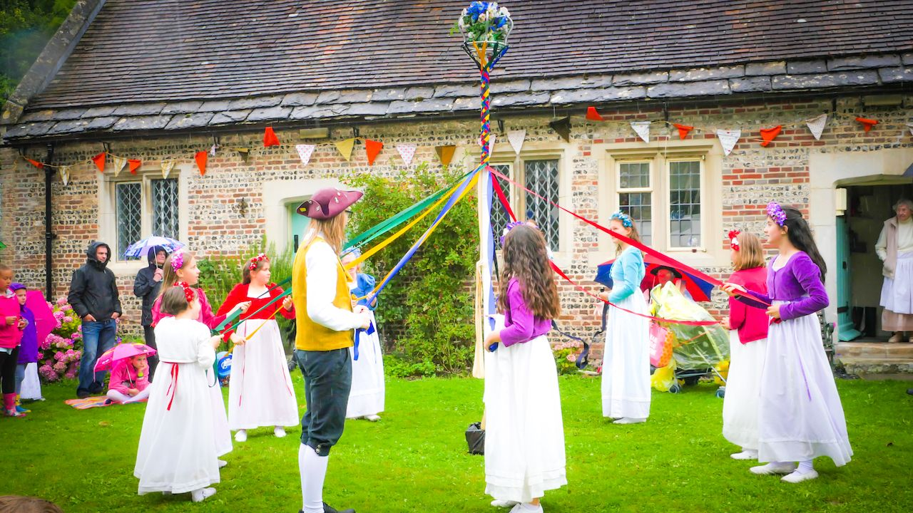 Children are dancing traditional dance at the 18th century street in Milton Abbas village, Dorset, UK
