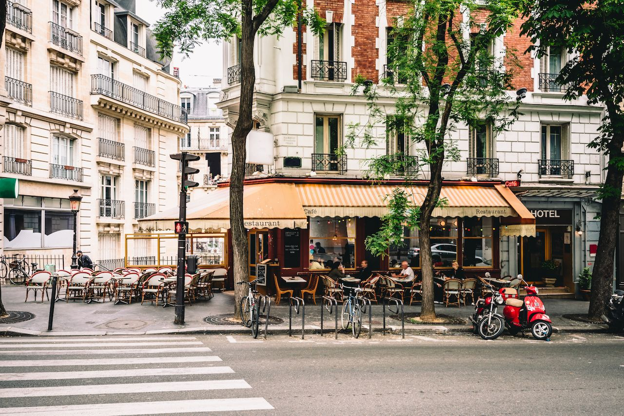 Cozy street with tables of coffee in quarter Montmartre in Paris, France