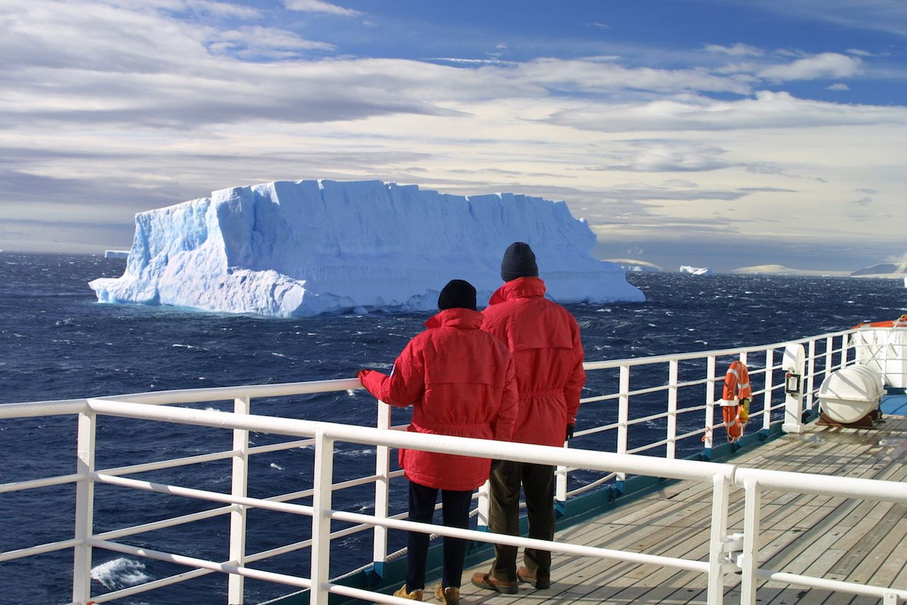 Cruise ship passengers looking at a beautiful iceberg at Antarctica