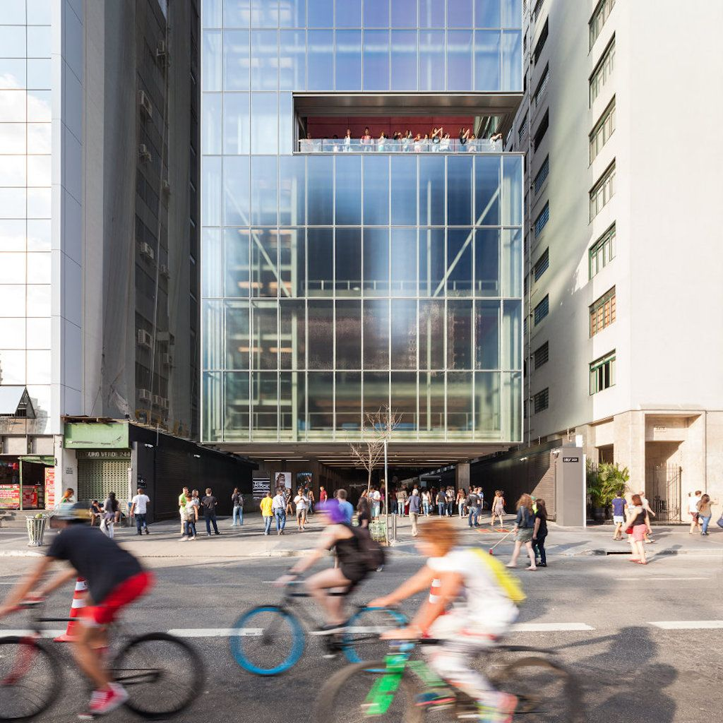 Cyclists in front of a glass building in Sao Pualo