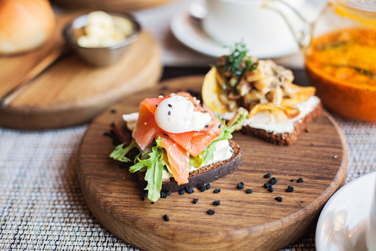 Danish sandwich with salmon fish and egg on wooden board