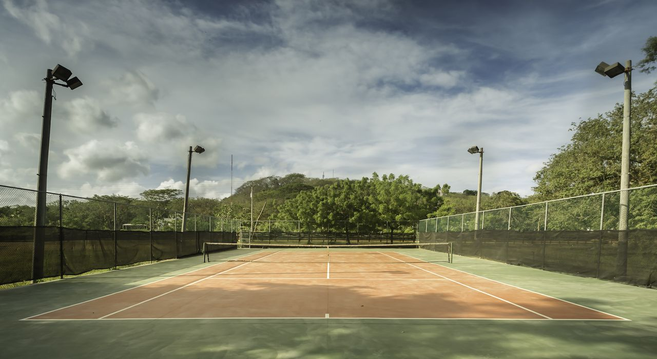 Empty resort tennis court under blue but cloudy skies
