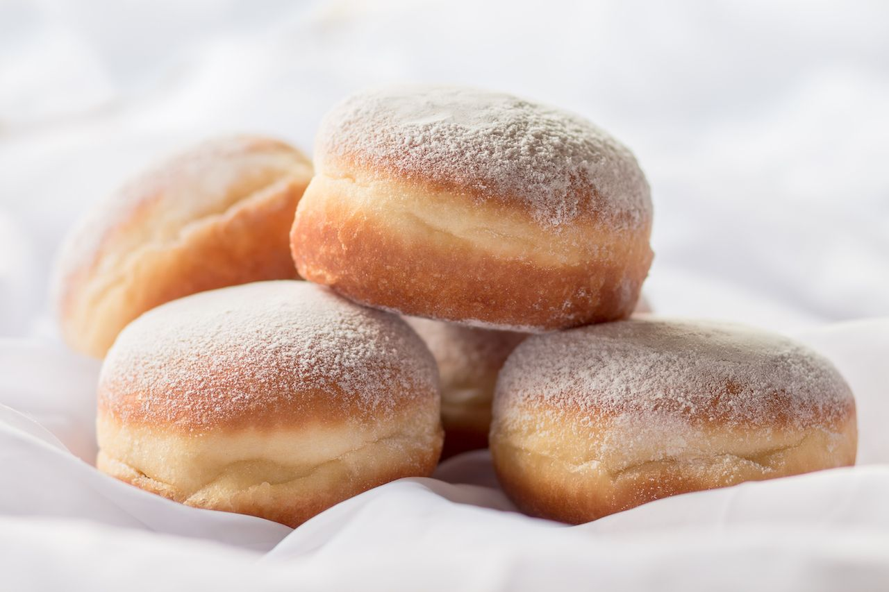 Jelly filled donuts with powdered sugar on a bed with white sheets