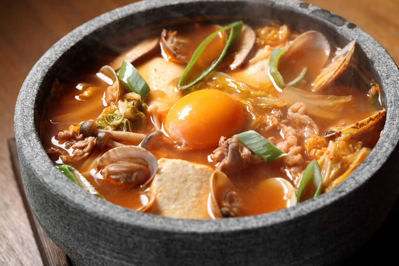 Korean soup with mushrooms, chives, and a raw egg yoke