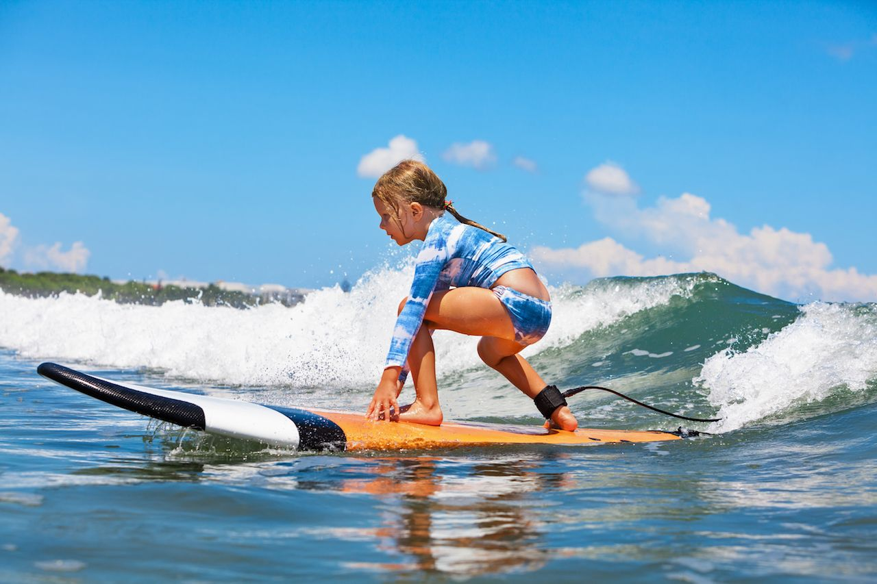 Little girl on a surf board riding a wave