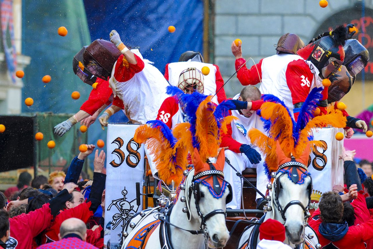 Masked people with traditional helmets throwing oranges during the traditional Carnival Parade of Oranges Battle in Ivrea