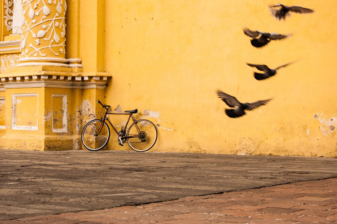 Pigeons take flight next to a bicycle leaning against a yellow church wall in Antigua, Guatemala