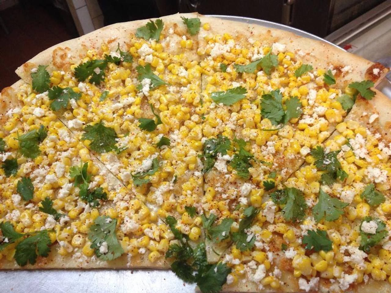 Pizza with corn, cheese, and an herb garnish