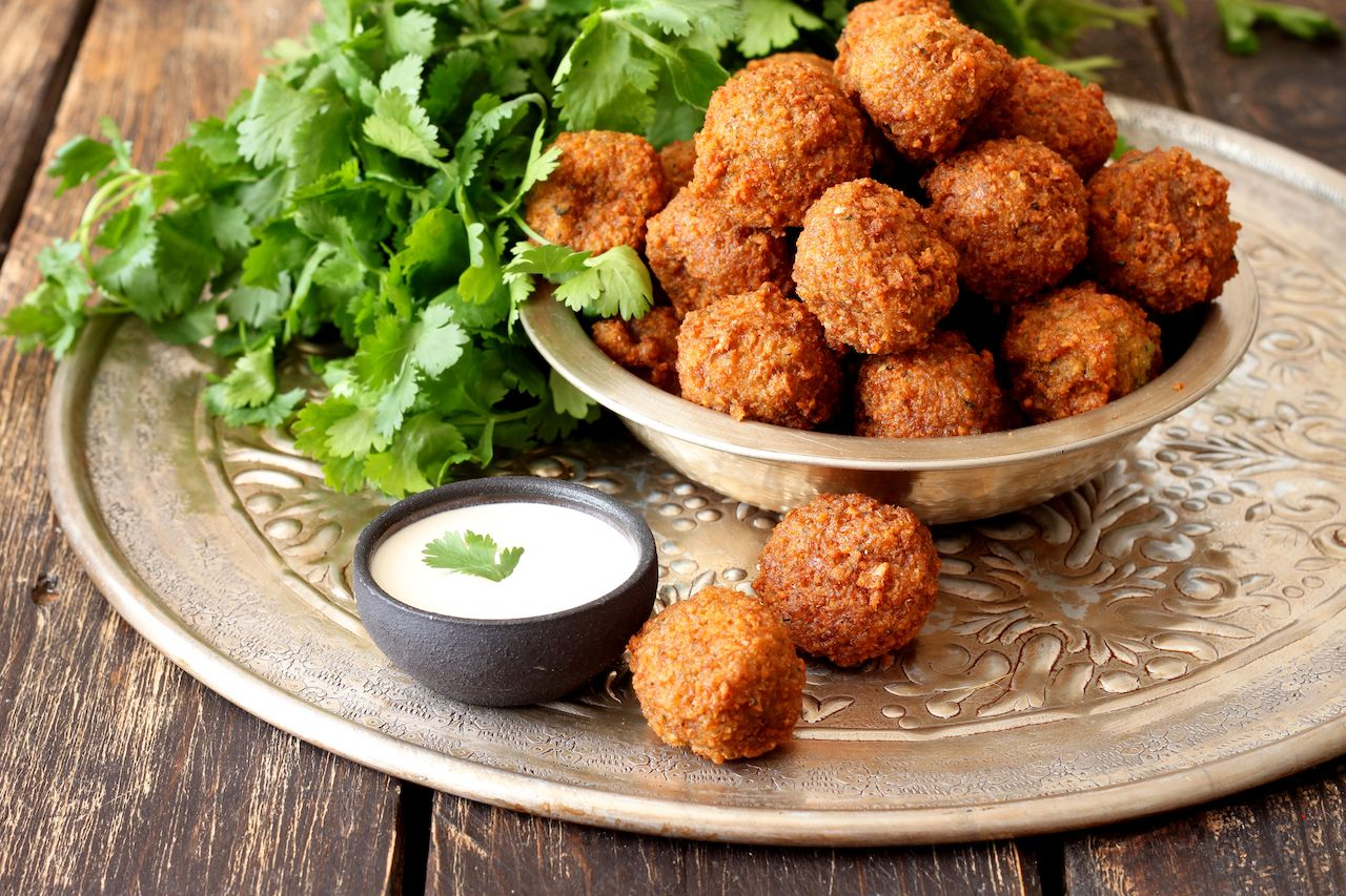 Platter of falafels with parsley and white dipping sauce