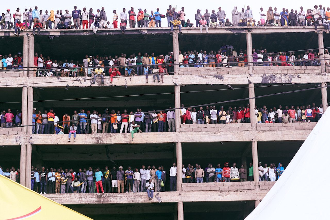 Rwandans lining the floors of an empty, open building to watch a cycling race
