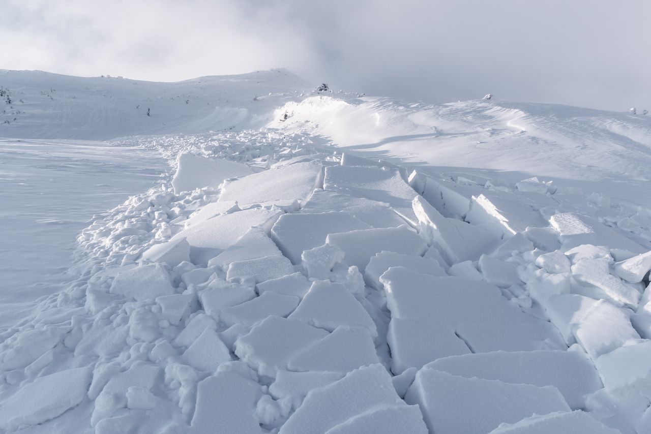 Snow avalanche in winter mountains