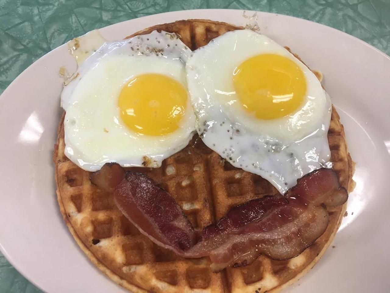 Tastee Diner overeasy eggs and a strip of bacon arranged on top of a waffle like a smiley face