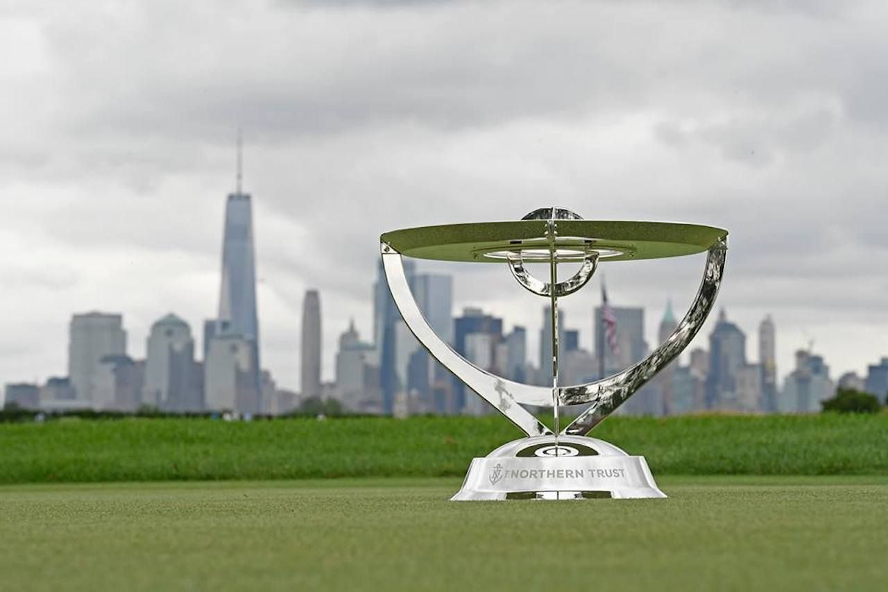 The Northern Trust trophy on a green with the city skyline in the background