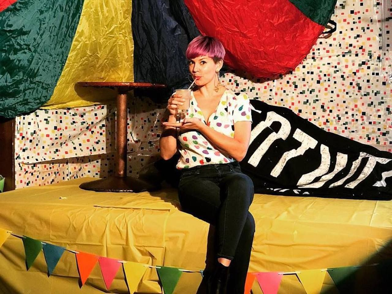 The STUD LGBTQ colorful decor with a girl drinking a cocktail