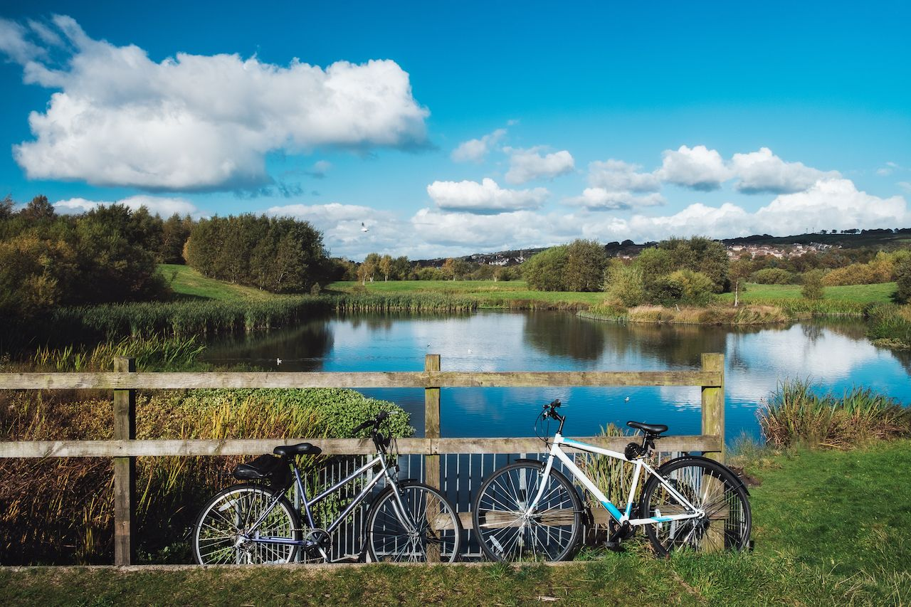 Two bicycles leaning against a fence opposite the picturesque lake in Bathgate, West Lothian, Scotland