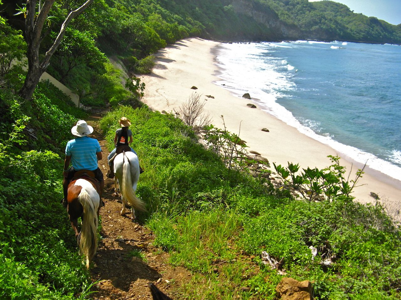 Two people riding horses through the greenery just off a Nicaraguan beach