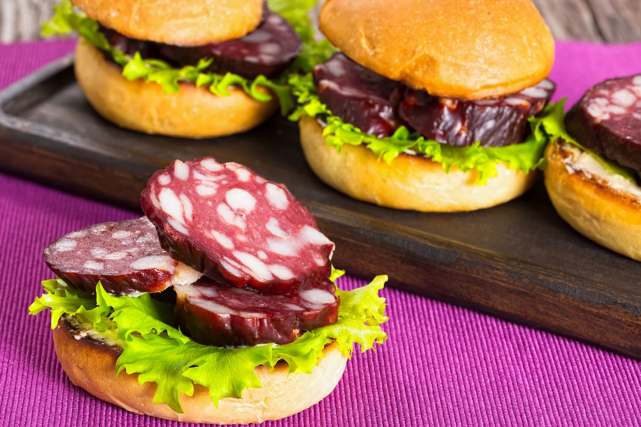 delicious sandwiches with butter, lettuce and slices of smoked sausage in fried bun on dark wooden board on table mat