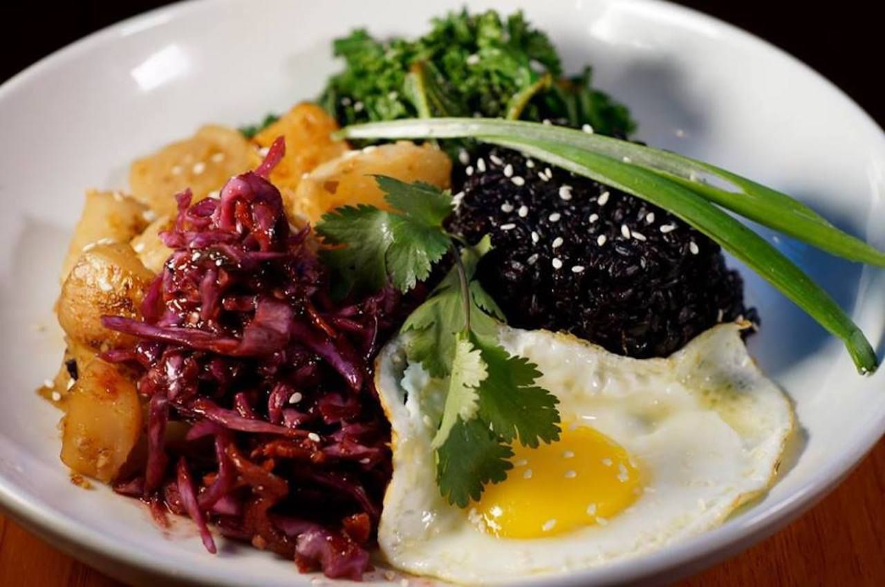 dish of black beans, slaw, potatoes, greens, and a fried egg