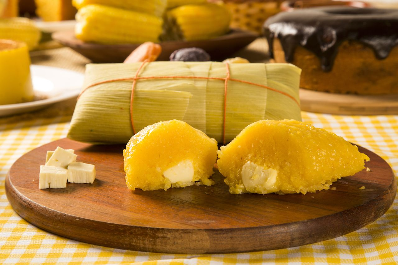 traditional corn dessert from a Brazil similar to a tamale on a wodden serving tray
