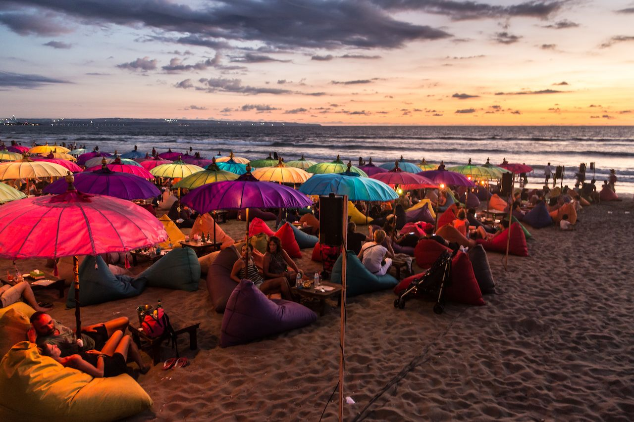 A large crowd of tourists enjoy the sunset at a bar on Kuta beach in Seminyak, Bali