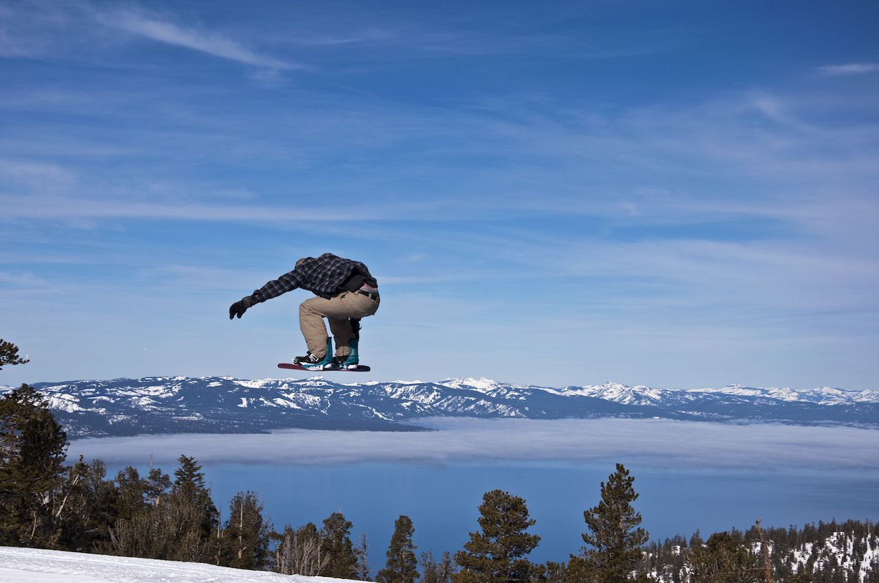 A snowboarder jumps over mountains and Lake Tahoe, California