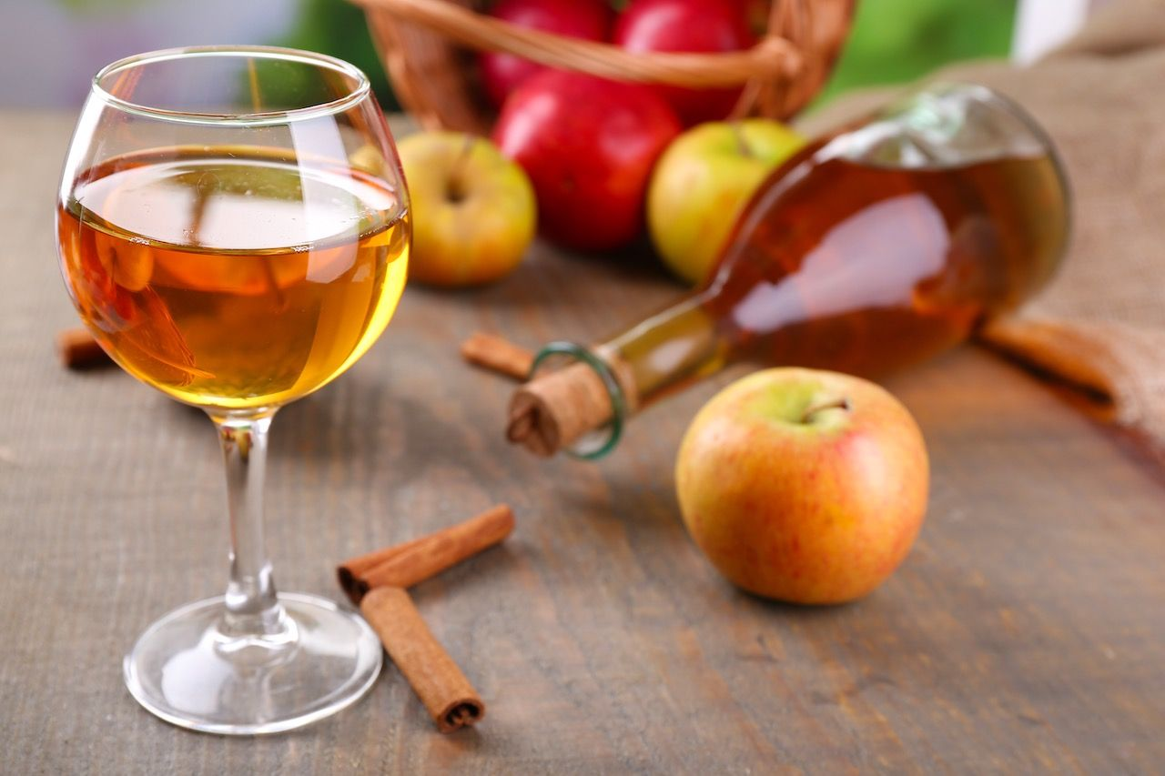 Apple cider in wine glass and bottle