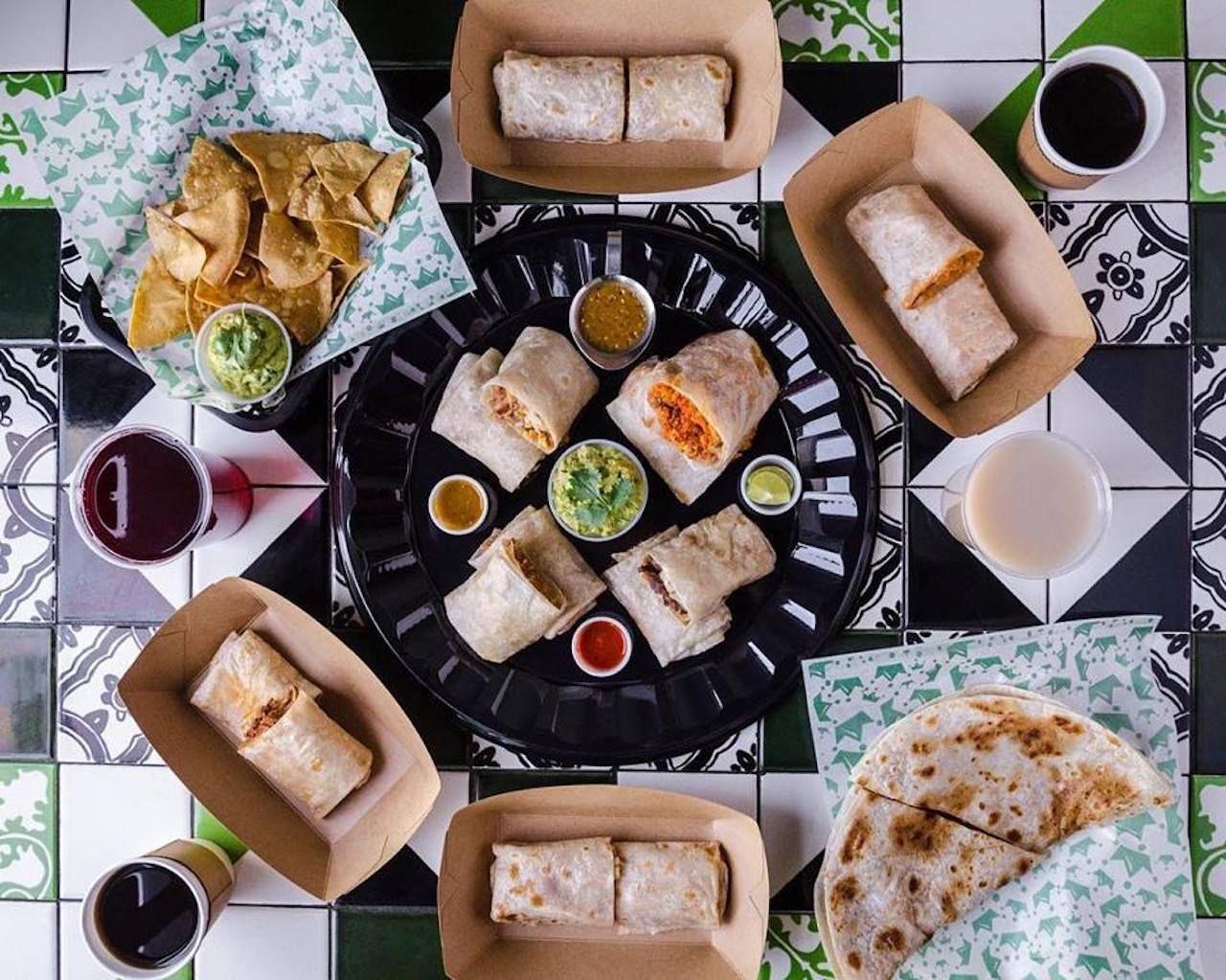 assortment of burritos with and other Mexican food