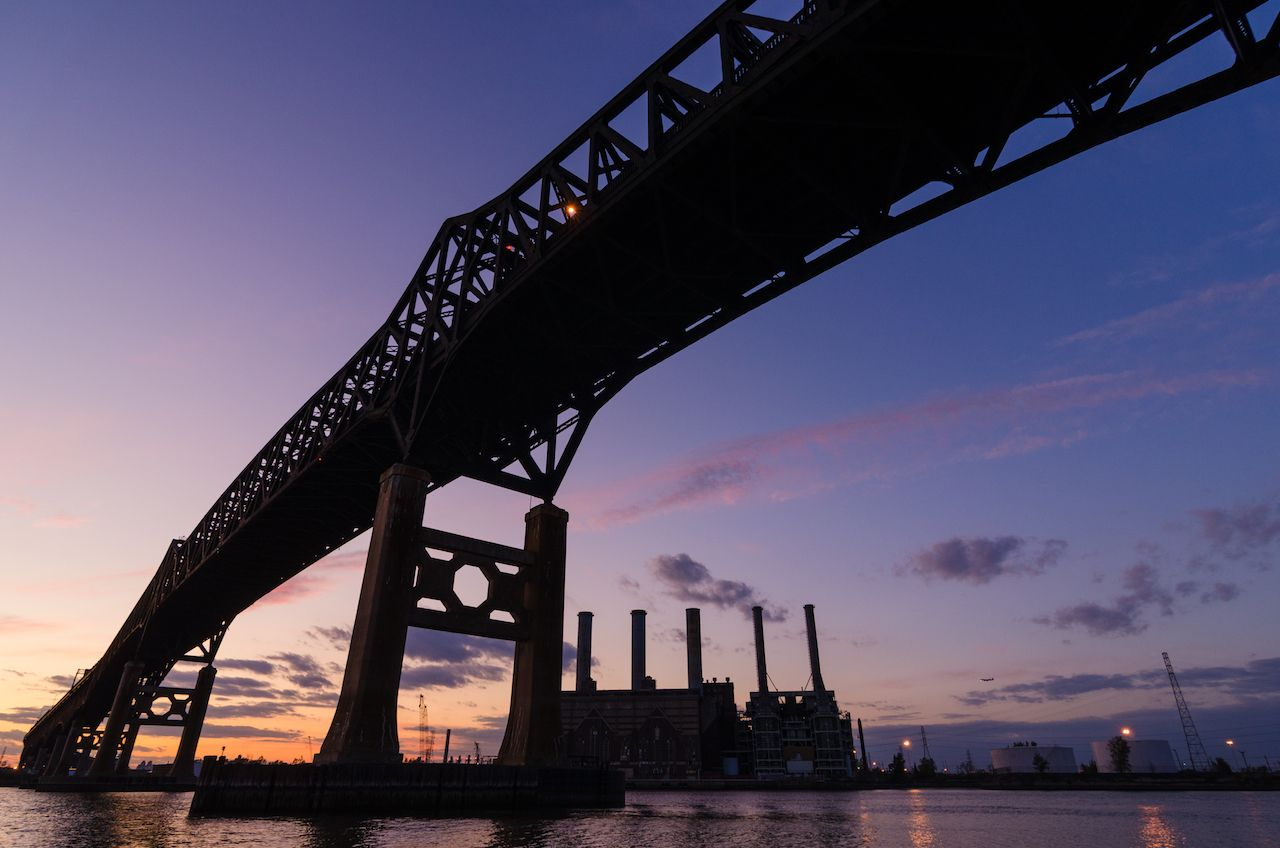 Bridge and industrial area silhouetted at sunset