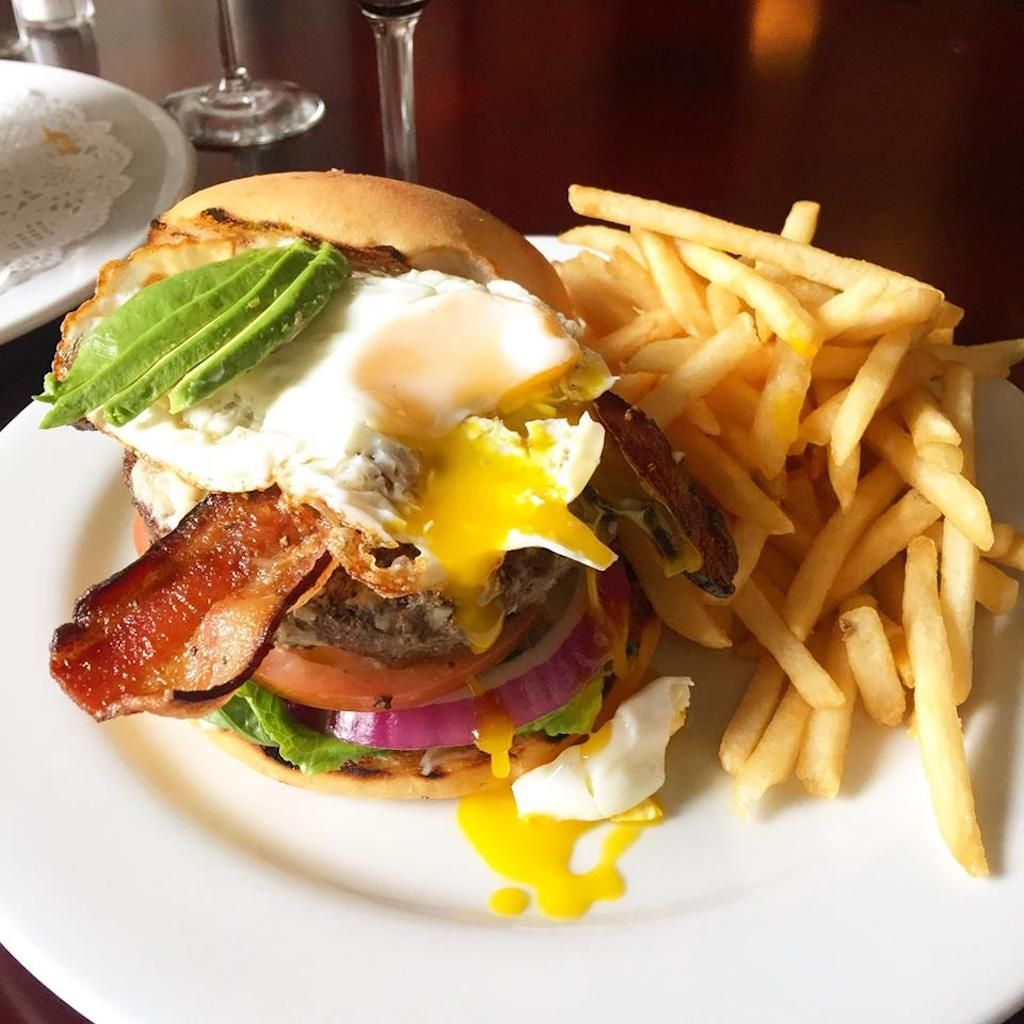 Burger with bacon, avocado, a fried egg, and french fries
