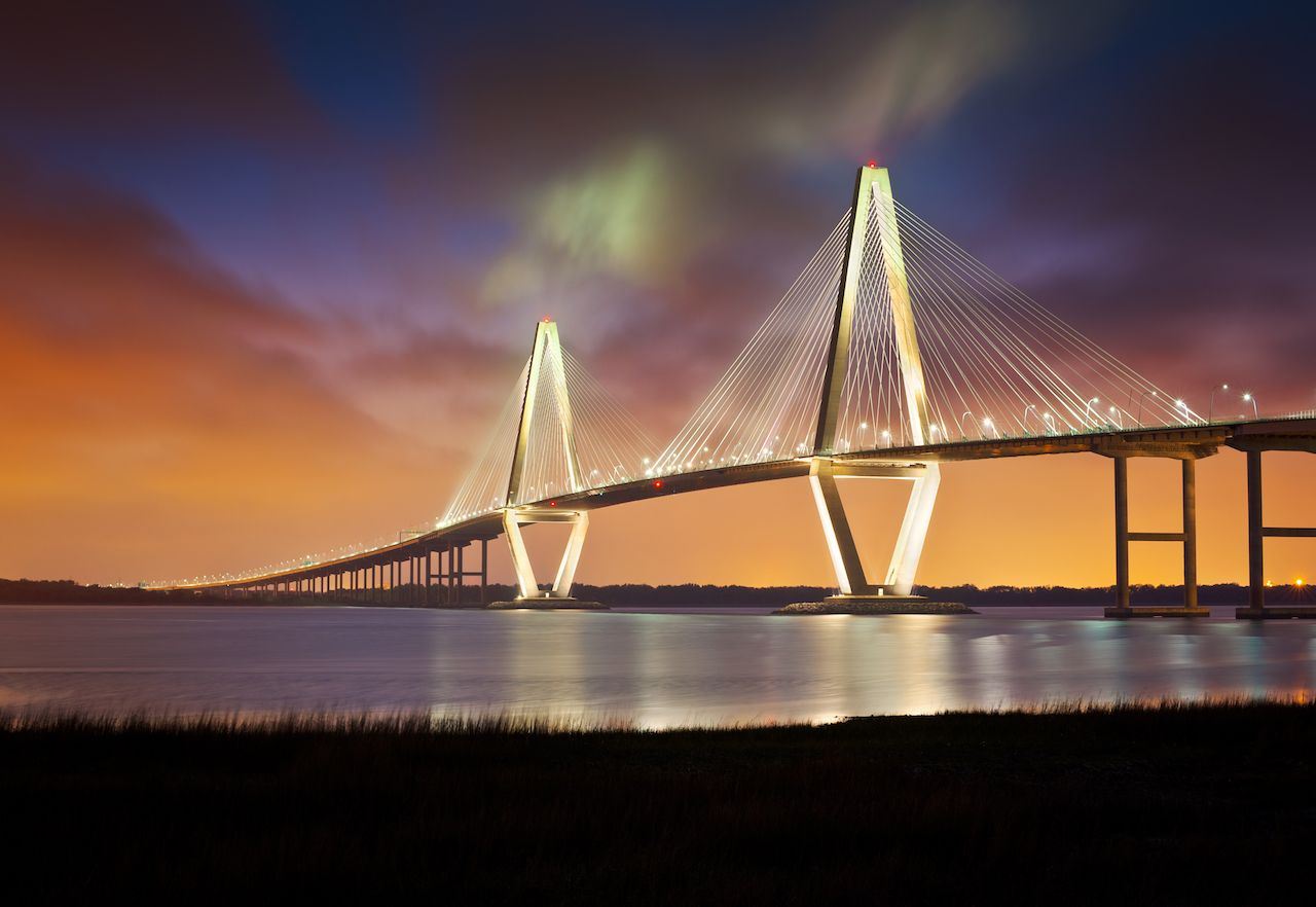 Charleston, South Carolina, bridge lit up under colorful sky