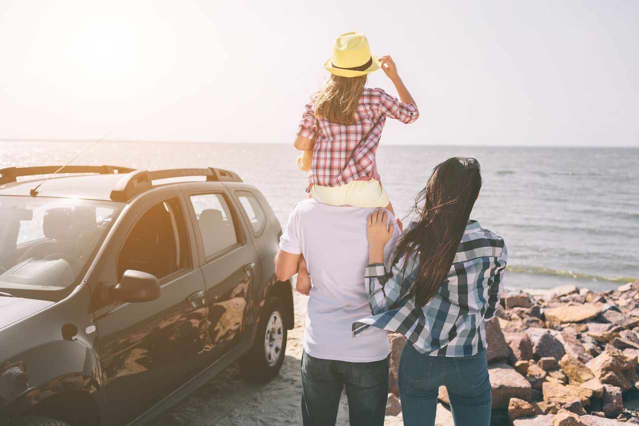 Family standing near a car on the beach