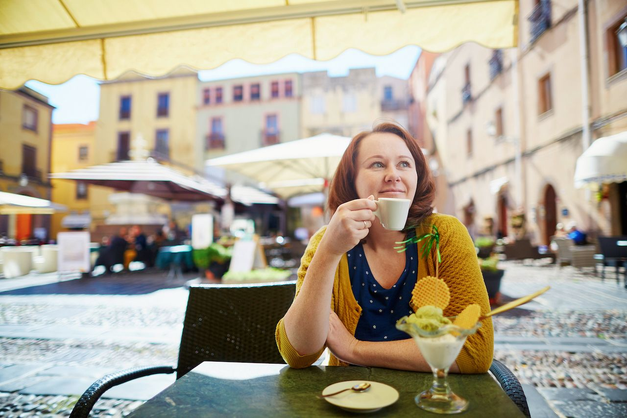 Girl drinking coffee and eating ice cream in cafe in Bosa village, Sardinia, Italy
