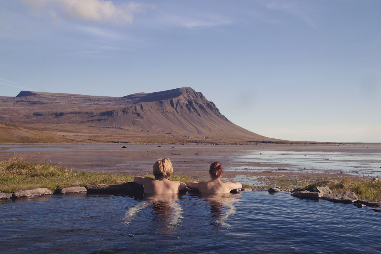 Happy couple in love bathing and relaxing in hot pool with spectacular view of wild landscape