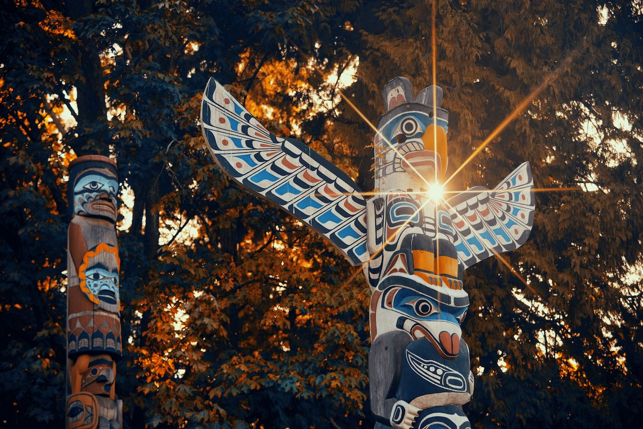 Indian totem poles with sun ray in Stanley park in Vancouver, Canada
