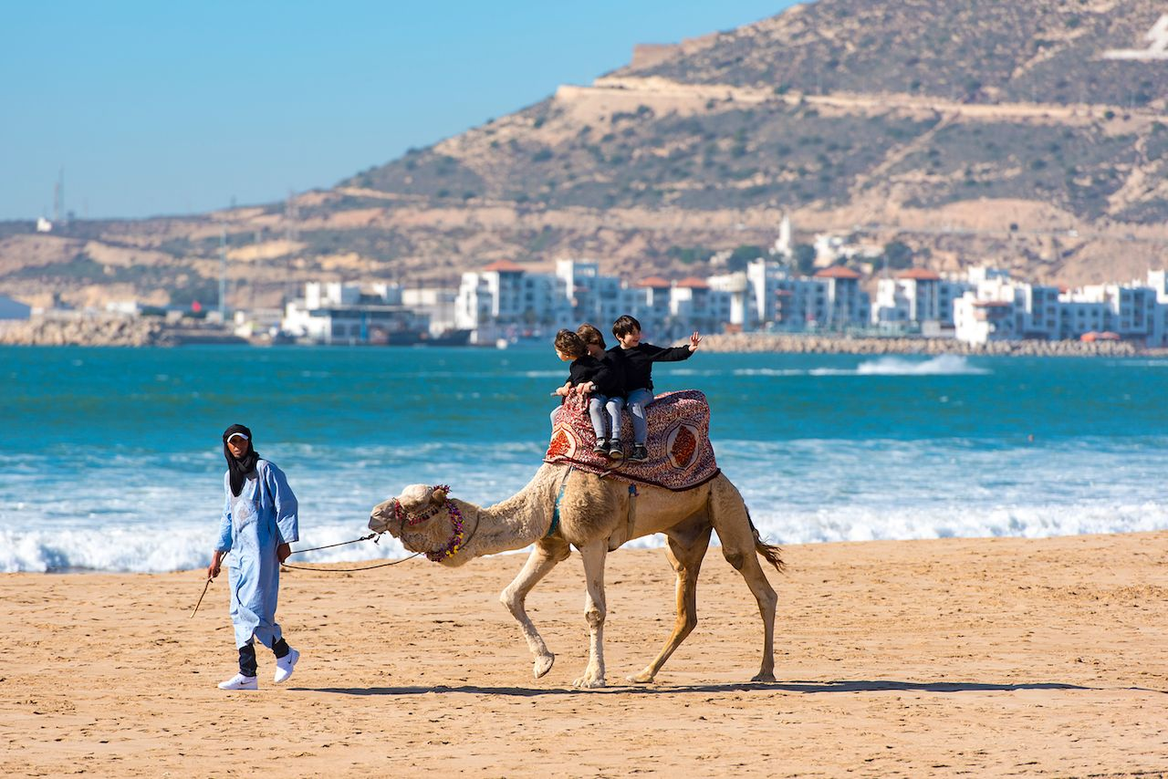 Kids riding a camel on the beach in Morocco