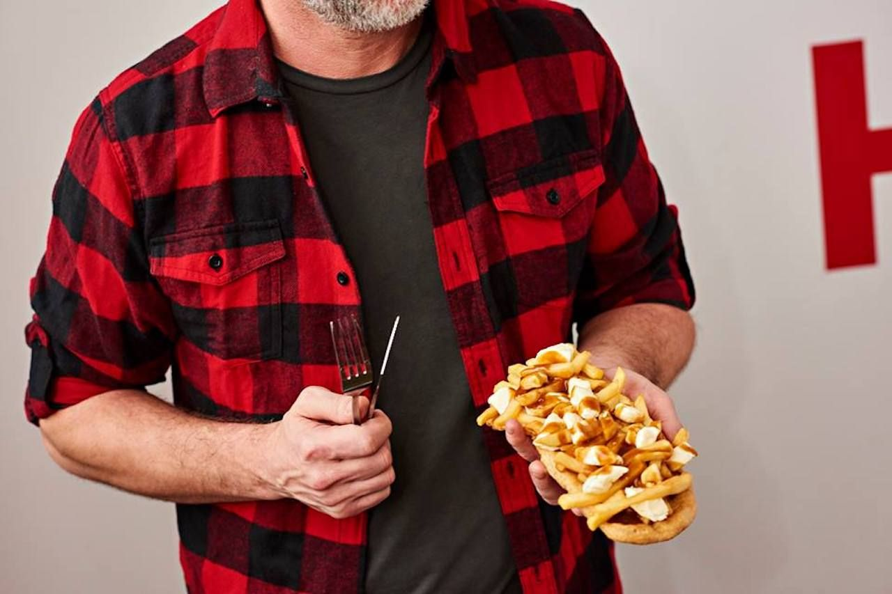 Man holding a BeaverTail topped with poutine