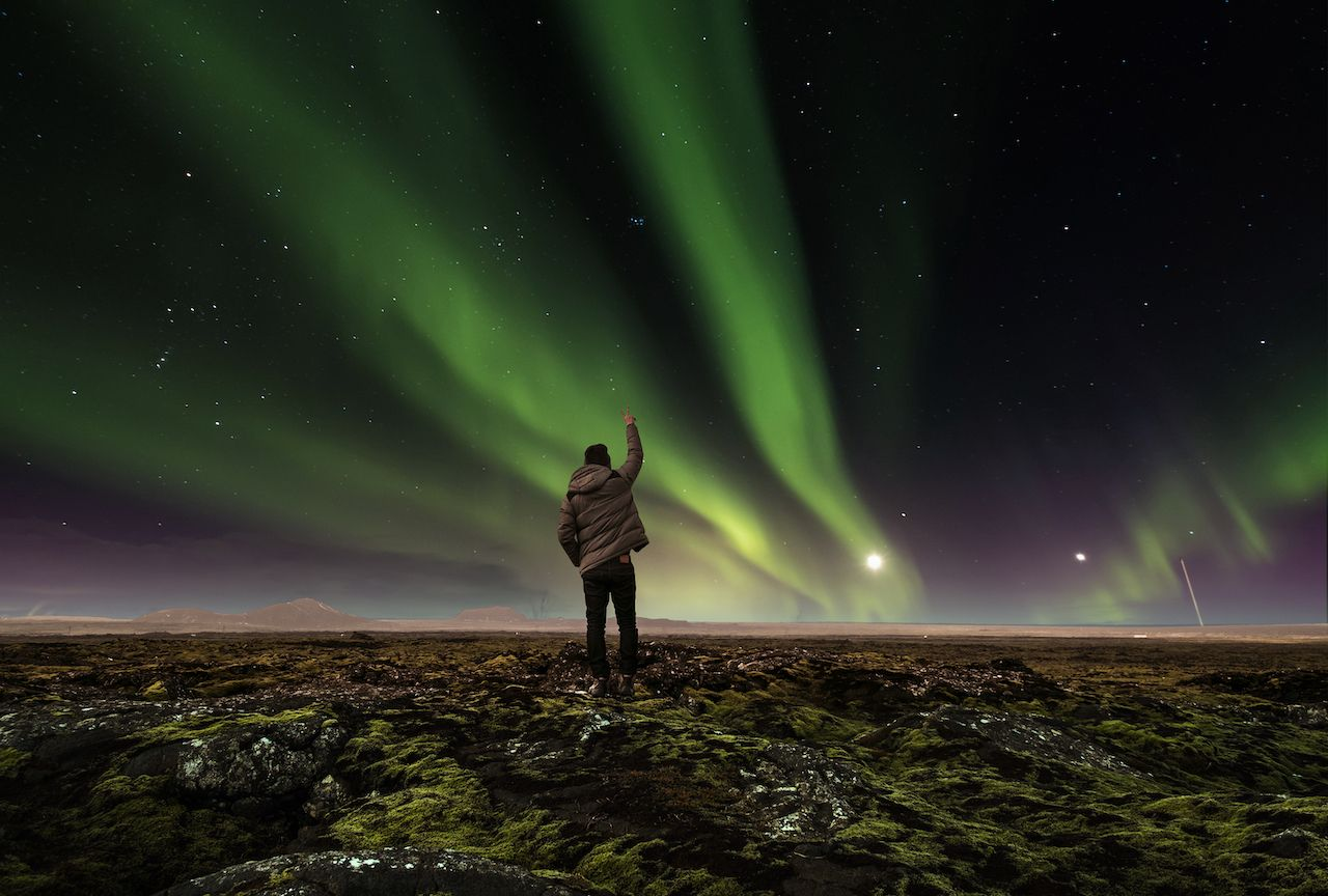 Man standing under the northern lights