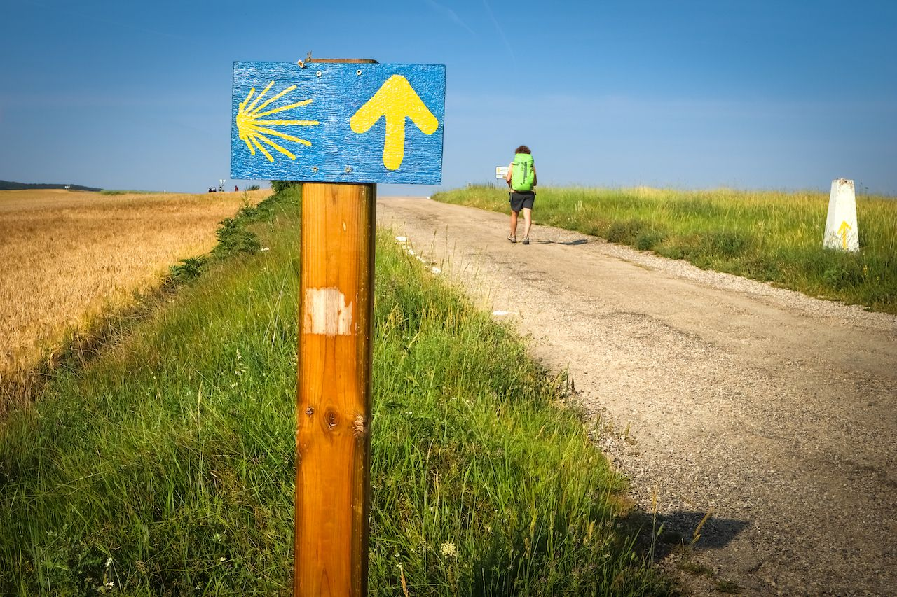 Milemarker and hiker on the Camino de Santiago