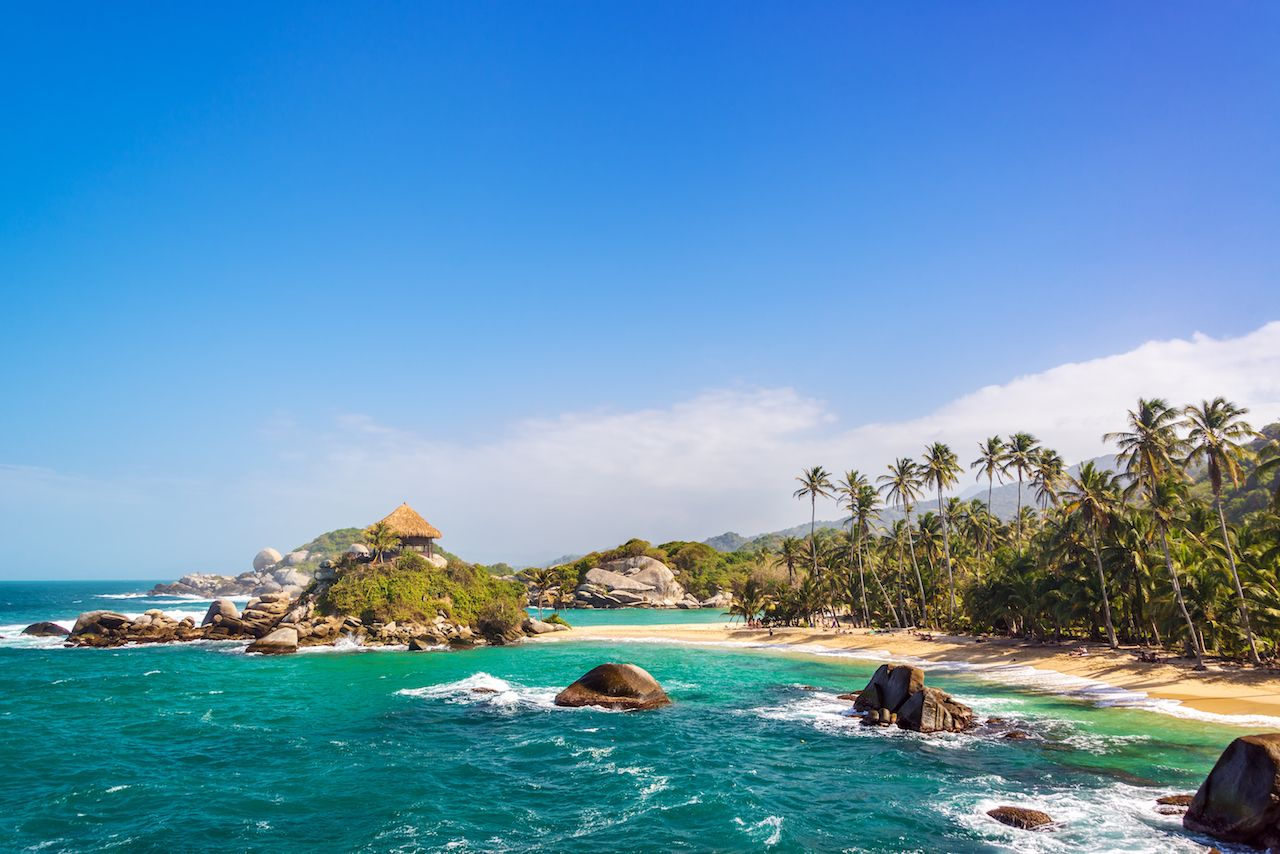 Palm trees and blue Caribbean water on San Juan del Guia beach in Tayrona National Park in Colombia