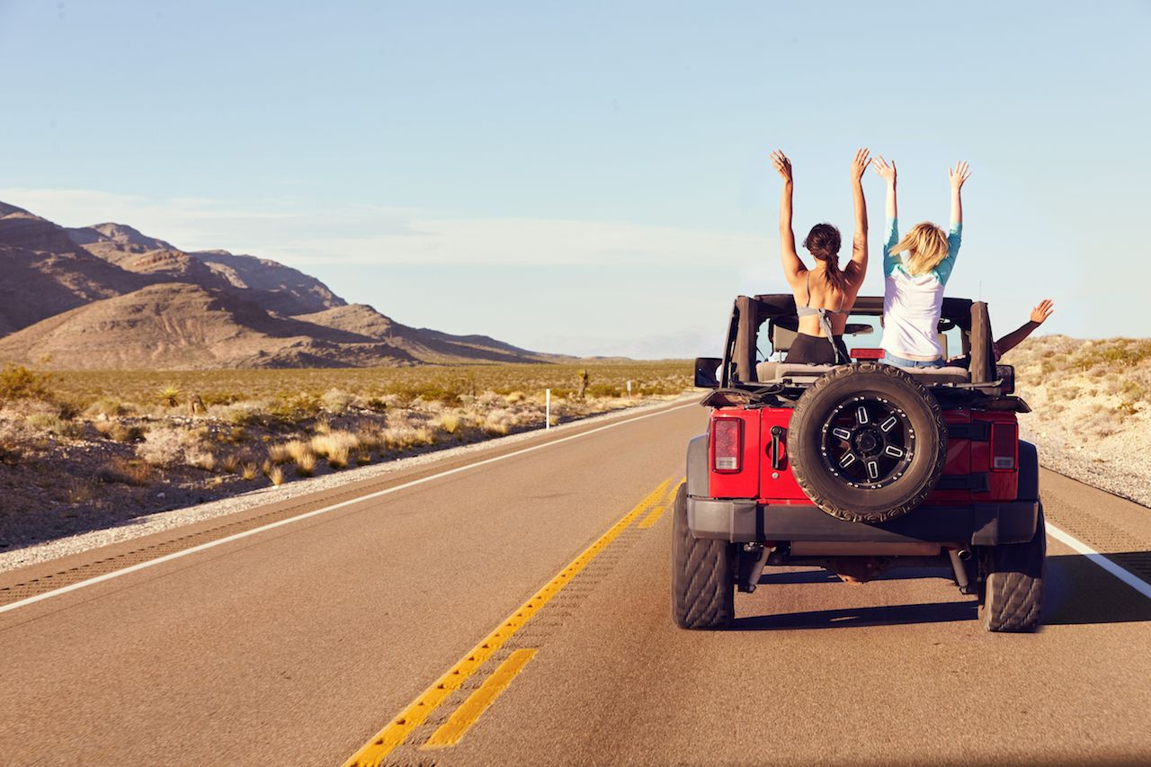 Rear View Of Friends On Trip Road Driving In Convertible Car