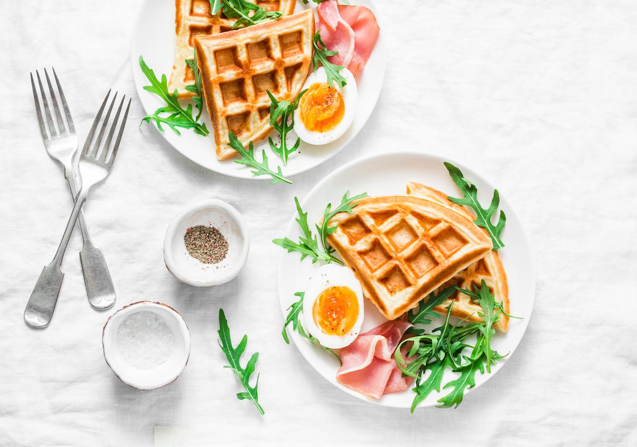 Served breakfast with potatoes savory waffles, boiled egg, ham and arugula on light background