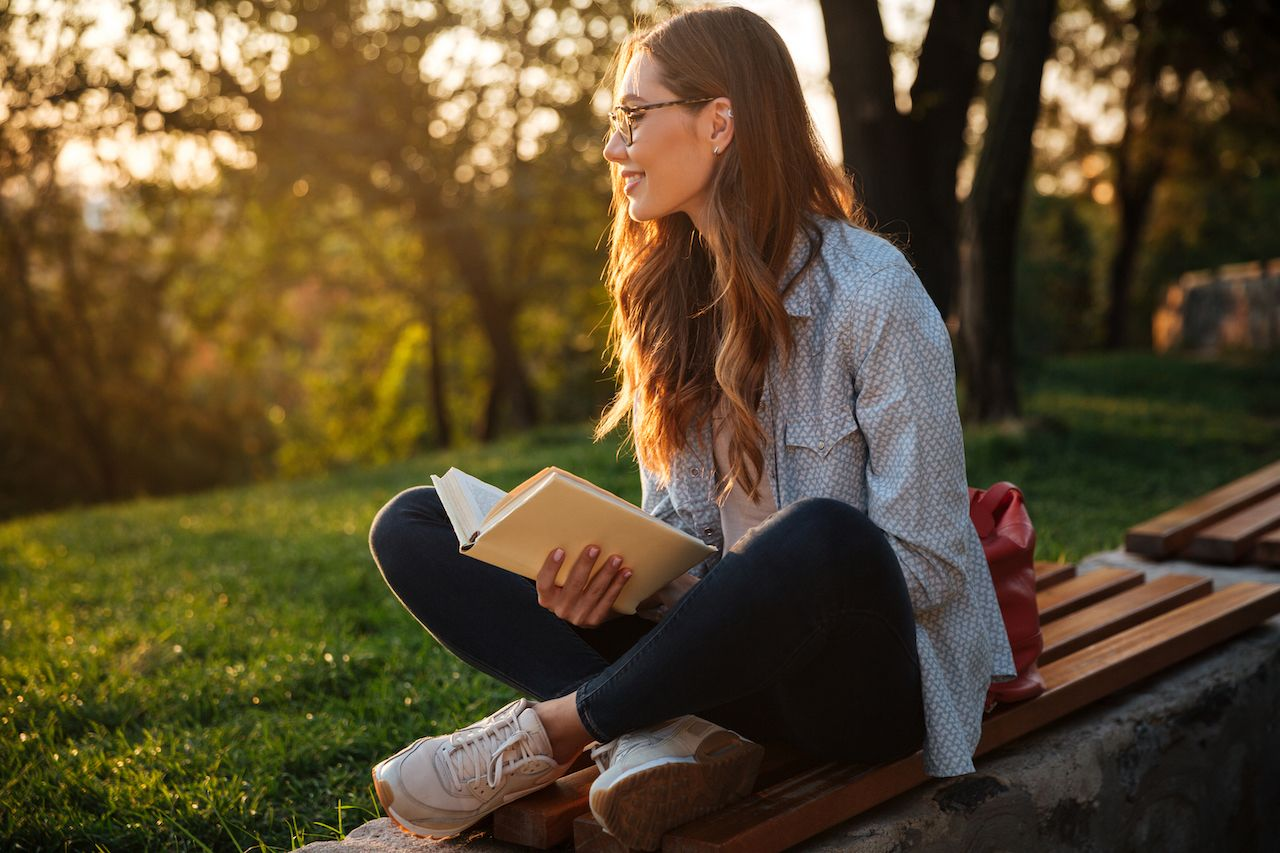 Side view of happy brunette woman in eyeglasses sitting on bench and holding book while looking away in park