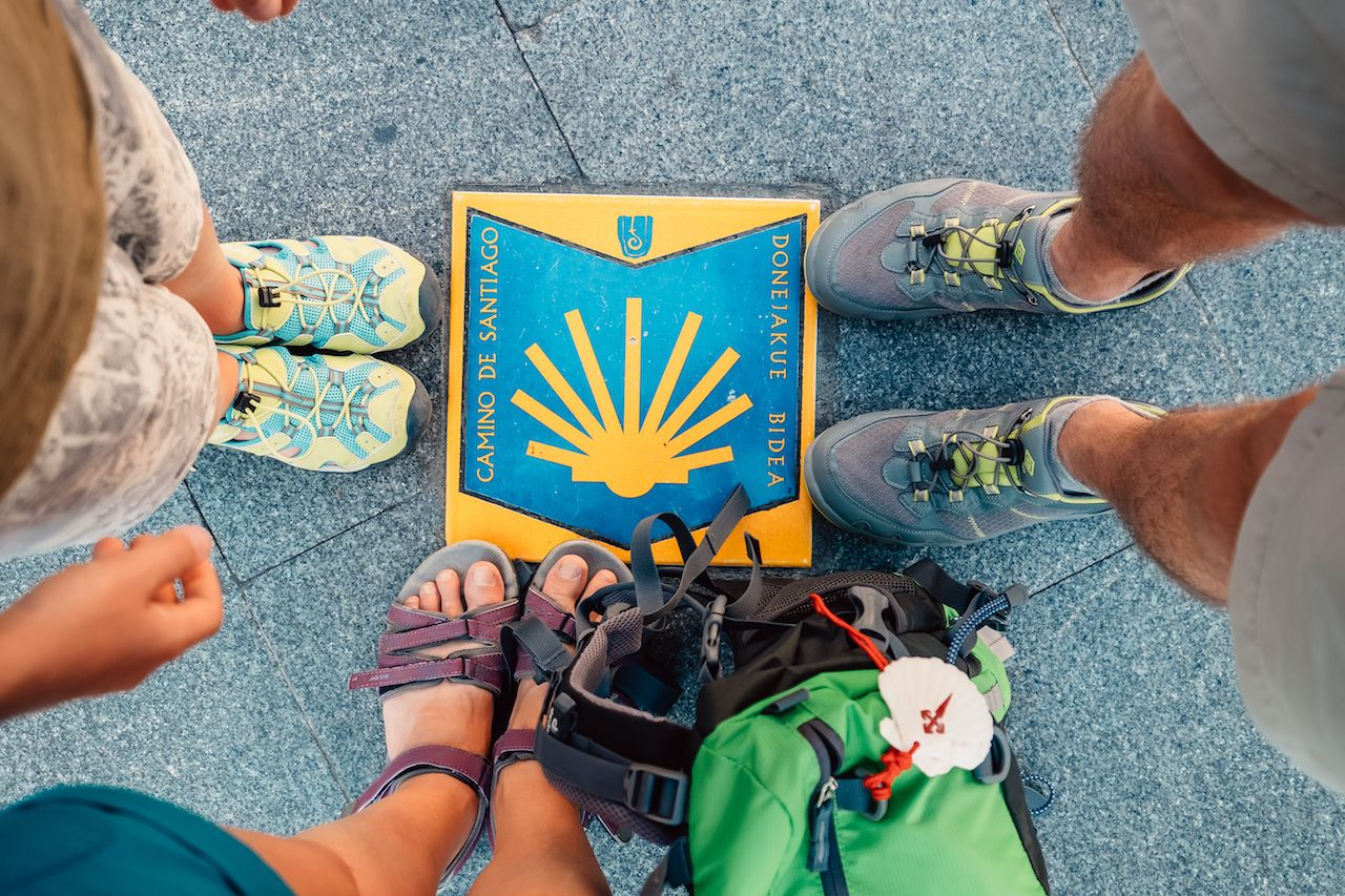 Three peers piligrims feet on the start of the Camino de Santiago