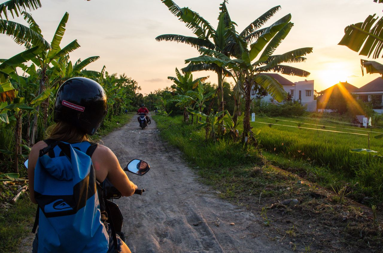 Woman drives with scooter along a smaller road in the Canggu area, Bali, Indonesia