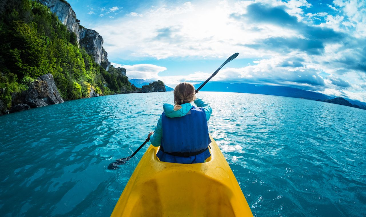 Woman paddles kayaking in the lake with turquoise water